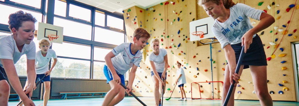 Leerlingen spelen hockey in gymlokaal